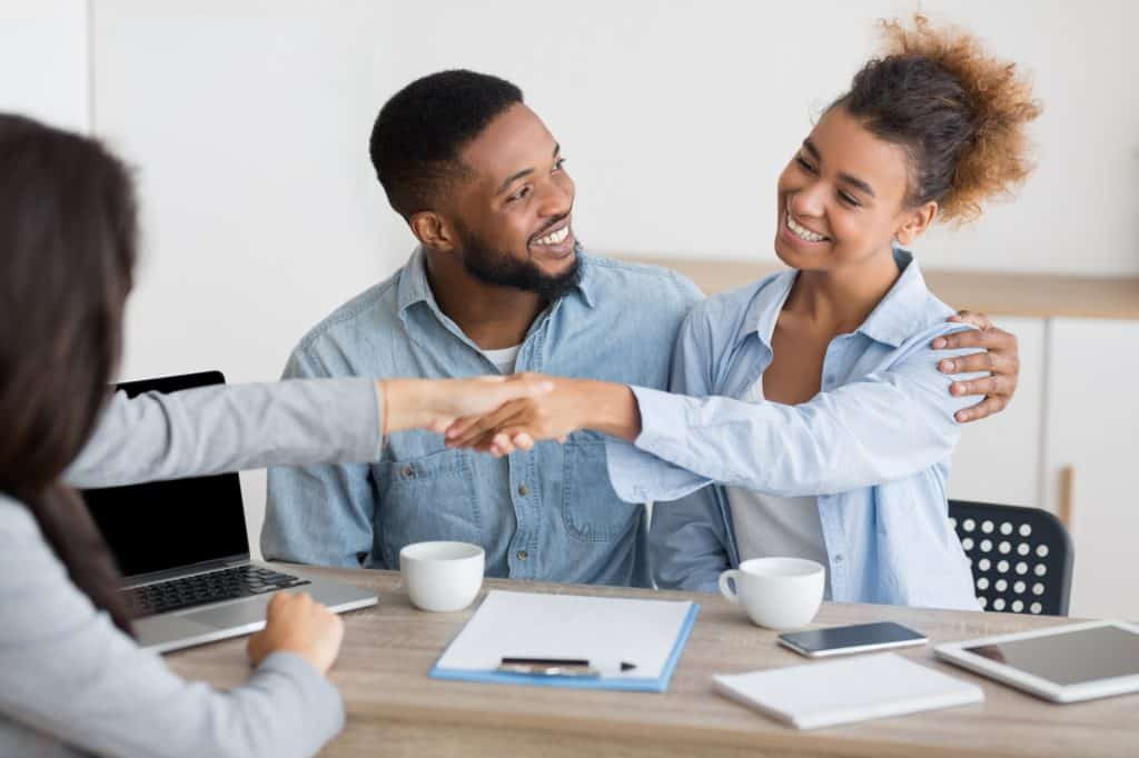 cheerful afro spouses and finansial counselor handshaking in office